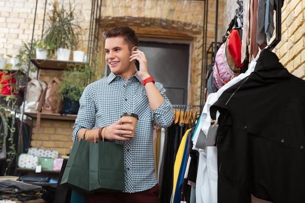 Przyjemny dzień. wesoły emocjonalny młody człowiek czuje się szczęśliwy i uśmiecha się stojąc w sklepie z ubraniami i rozmawiając przez telefon