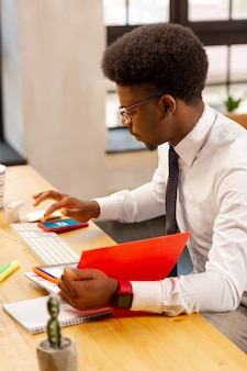 Przyjemny młody człowiek naciska ekran swojego smartfona, jednocześnie odwracając uwagę od pracy