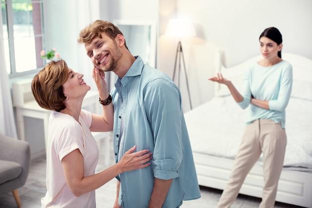Przyjemny nastrój. szczęśliwa radosna kobieta patrząc na swojego syna, ciesząc się z nim czas