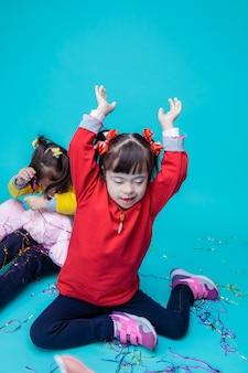Przyjemny nastrój. szczęśliwe dziewczynki z zaburzeniami genetycznymi bawiące się zabawkami i elementami dekoracyjnymi