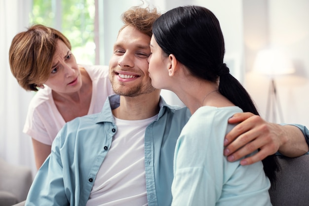 Przyjemny pocałunek. miły, szczęśliwy człowiek, uśmiechając się, gdy jest całowany przez swoją żonę