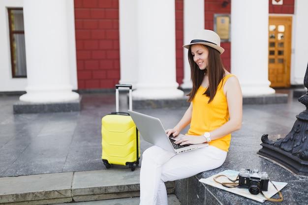 Przyjemny podróżnik turysta kobieta z walizką siedzieć na schodach za pomocą pracy na komputerze typu laptop w mieście na zewnątrz. dziewczyna wyjeżdża za granicę na weekendowy wypad. koncepcja życia podróż turystyka.