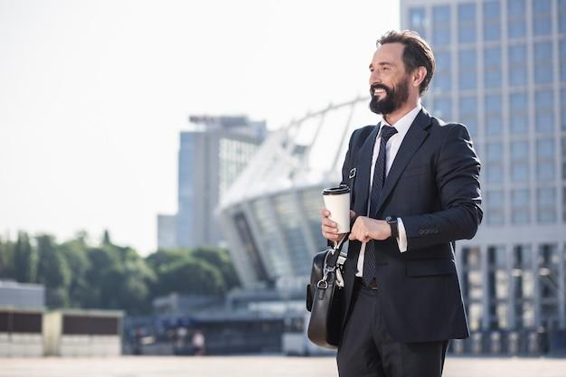 Przyjemny poranek. talia wesoły dorosły pracownik biurowy idzie do pracy podczas picia kawy