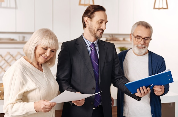 Przyjemny proces udostępniania informacji. pewny siebie, doświadczony, uśmiechnięty prawnik pracujący i prezentujący kontrakt starszej parze klientów, wyrażający jednocześnie pozytywne nastawienie