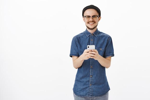 Przyjemny, przystojny młody mężczyzna z brodą i wąsami w okularach i czarnej czapce trzymający smartfona, wpatrując się w zachwycający, radosny uśmiech
