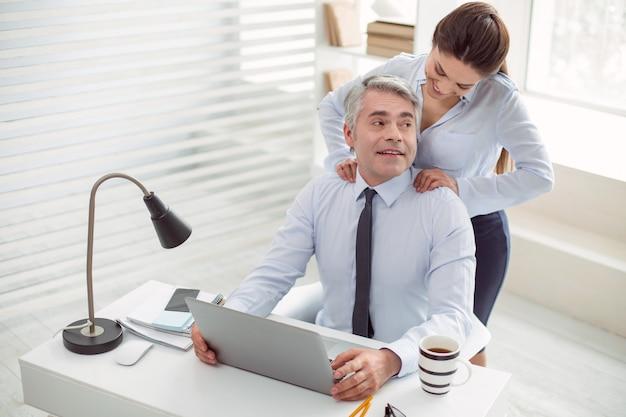 Przyjemny relaks. miły pozytywny szczęśliwy człowiek uśmiecha się i siedzi przy stole podczas masażu