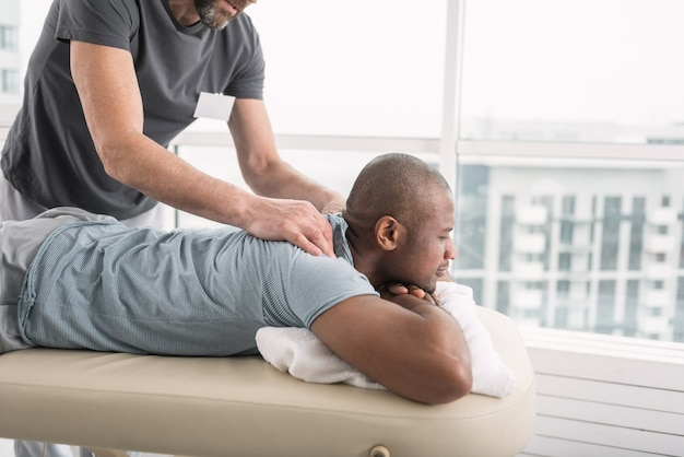 Przyjemny relaks. przyjemny przystojny mężczyzna korzystający z masażu podczas wizyty w centrum medycznym
