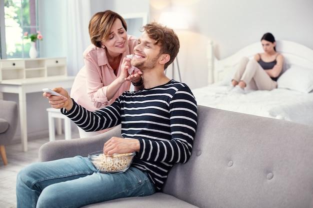 Przyjemny relaks. wesoły dorosły mężczyzna wybiera kanał telewizyjny, ciesząc się relaksem