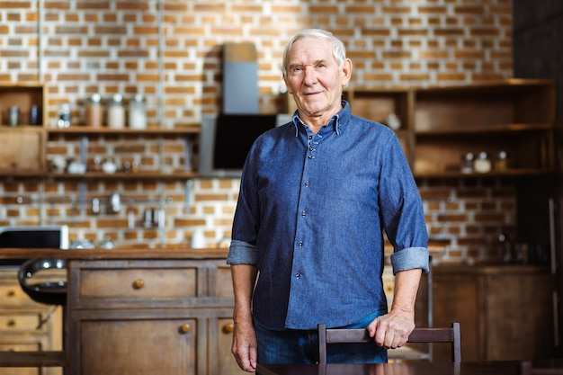 Przyjemny starszy mężczyzna stojący w kuchni, czując się szczęśliwy w domu