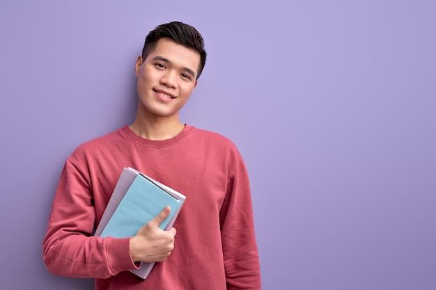 Przyjemny student z azji z książką w rękach cieszy się edukacją i uniwersytetem