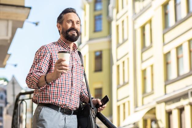 Przyjemny styl życia. radosny przystojny mężczyzna pije kawę, przygotowując się do rozpoczęcia nowego dnia