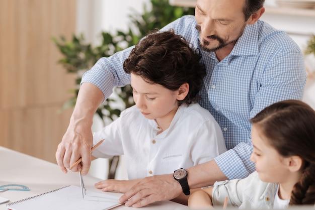 Przyjemny uśmiechnięty mężczyzna czule trzymający za rękę syna próbującego narysować okrąg, podczas gdy jego córka obserwuje proces