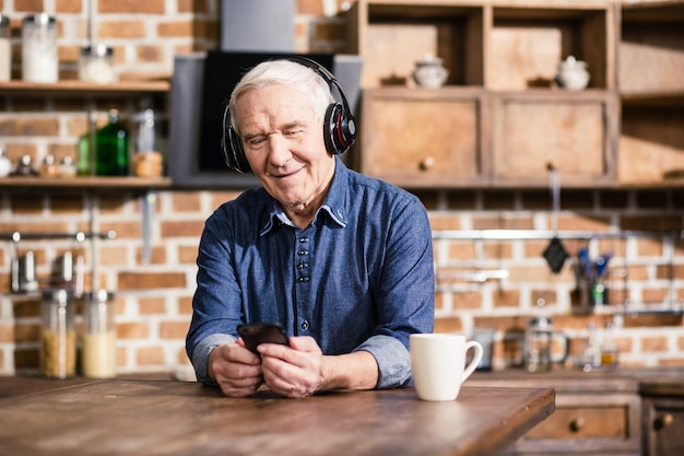 Przyjemny uśmiechnięty starszy mężczyzna przy użyciu swojego smartfona podczas słuchania muzyki