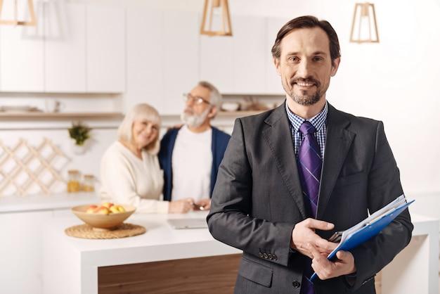 Przyjemny wynik. uśmiechnięty szczęśliwy zachwycony notariusz pracujący i trzymający ważne dokumenty