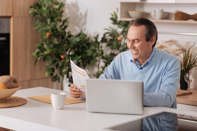 Przyjemny, zachwycony starzejący się mężczyzna siedzi w domu, czytając czasopismo i używając laptopa