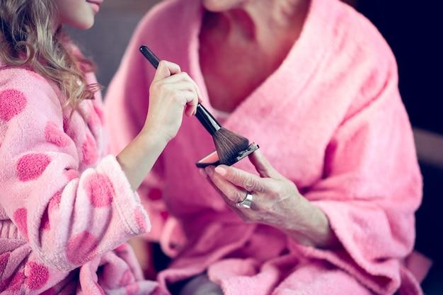 Przyjmowanie pudru do twarzy. zbliżenie na dziewczynę i jej babcię w różowych szlafrokach biorących puder do twarzy podczas robienia makijażu