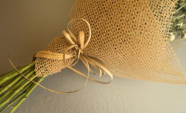 Przykład pakowania bukietu kwiatów w brązową siatkę kwiatową, zbliżenie