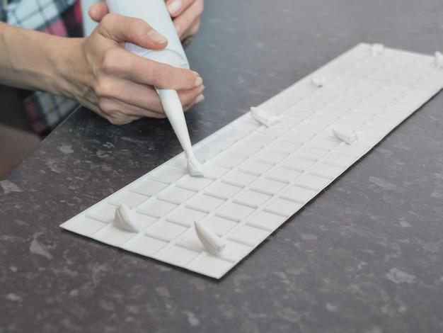 Przyklejanie plastikowego panelu z białej deski do ściany za pomocą pistoletu do klejenia, silikonowej rurki