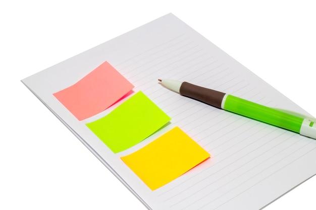 Przyklejony papier z pustym miejscem na tekst lub wiadomość, otwarty notatnik i długopis obok. odosobniony