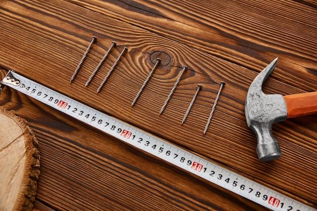 Przykręć gwoździe, młotek i miarkę do drewnianego stołu. profesjonalny instrument, sprzęt stolarski, elementy złączne, narzędzia do mocowania i wkręcania
