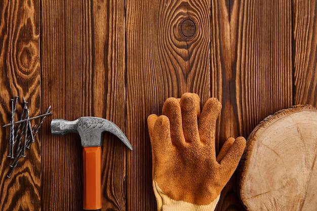 Przykręć gwoździe, młotek i rękawicę na drewnianym stole. profesjonalny instrument, sprzęt stolarski, elementy złączne, narzędzia do mocowania i wkręcania
