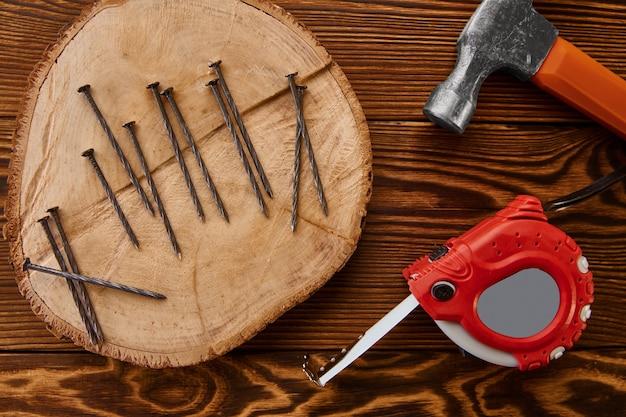 Przykręć gwoździe, młotek i taśmę mierniczą na drewnianym stole, widok z góry. profesjonalny instrument, sprzęt stolarski, elementy złączne, narzędzia do mocowania i wkręcania