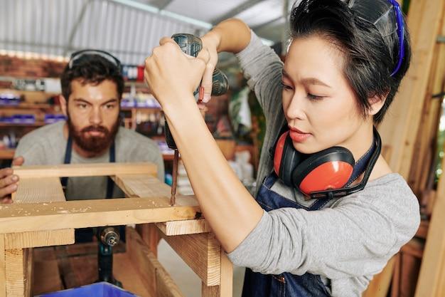 Przykręcanie części drewnianego stołka