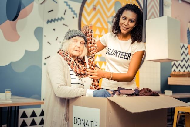 Przymierz to. miła afro amerykanka uśmiechnięta, pomagająca bezdomnej założyć szalik