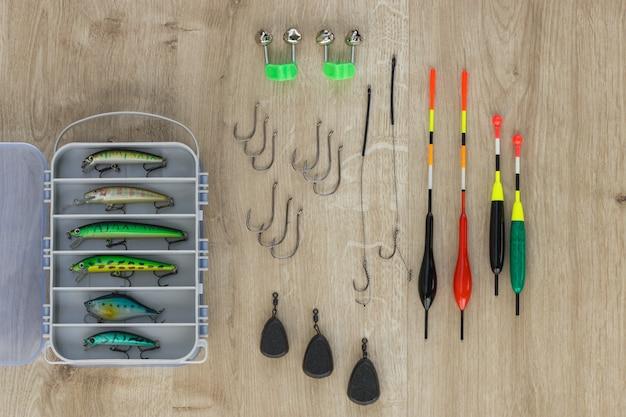 Przynęta wędkarska i haczyki, ciężarek, dzwonek i spławik na drewnianym stole. nowoczesna koncepcja połowów.