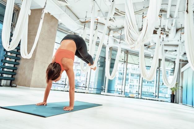 Przynieś harmonię swojemu ciału młoda wysportowana kobieta ćwicząca fly lub aerial jogę z