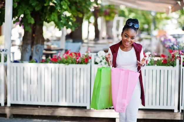 Przypadkowa amerykanin afrykańskiego pochodzenia dziewczyna z kolorowy torba na zakupy chodzić plenerowy. stylowa czarna kobieta na zakupy.