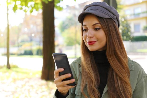 Przypadkowa dziewczyna w kapeluszu i szyi polo, pisząc na smartfonie na świeżym powietrzu