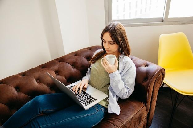 Przypadkowa kobieta relaksuje z laptopem