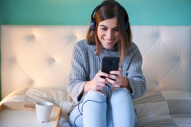 Przypadkowa kobieta słucha muzyka w jej sypialni
