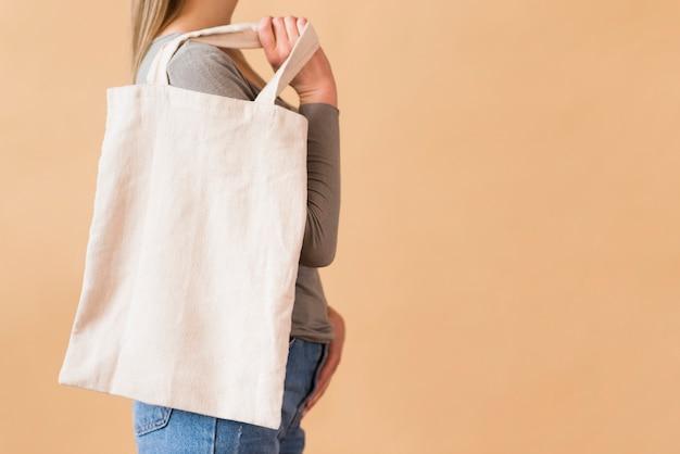 Przypadkowa młoda kobieta trzyma torbę wielokrotnego użytku