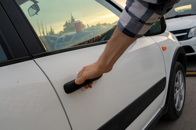 Przypadkowa osoba otwiera białe drzwi samochodu na parkingu, koncepcja wynajmu samochodu