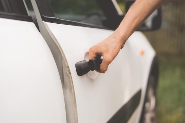 Przypadkowa osoba otwiera białe drzwi samochodu na parkingu