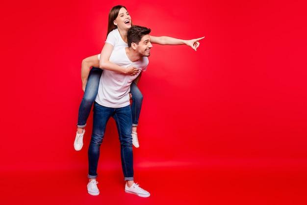 Przypadkowa para pozuje na czerwonej ścianie