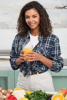 Przypadkowa ubierająca kobieta trzyma szkło sok