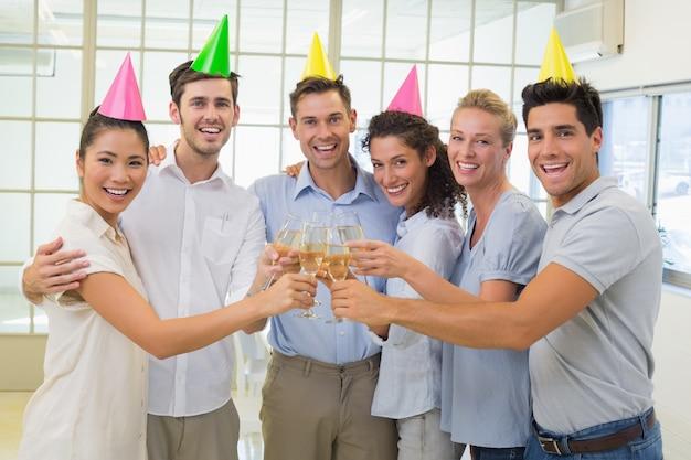 Przypadkowa uśmiechnięta biznes drużyna wznosi toast z szampanem