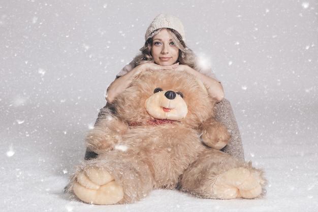 Przypadkowa uśmiechnięta młoda kobieta trzyma dużego miękkiego misia na śnieżnym tle w trykotowym ubraniu