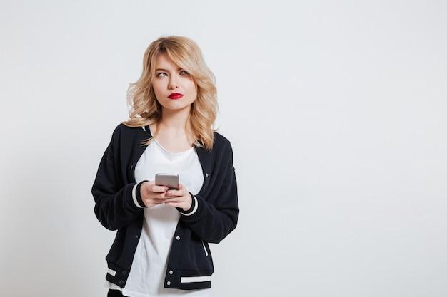 Przypadkowa zadumana kobieta trzyma telefon komórkowego i patrzeje daleko od