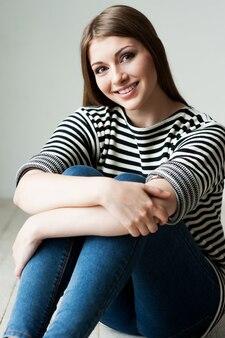 Przypadkowe piękno. piękna młoda kobieta w pasiastym ubraniu siedzi na podłodze i uśmiecha się
