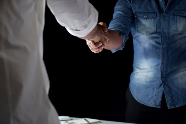 Przypadkowi biznesmeni robi uściskowi dłoni podczas spotkania przy nocą