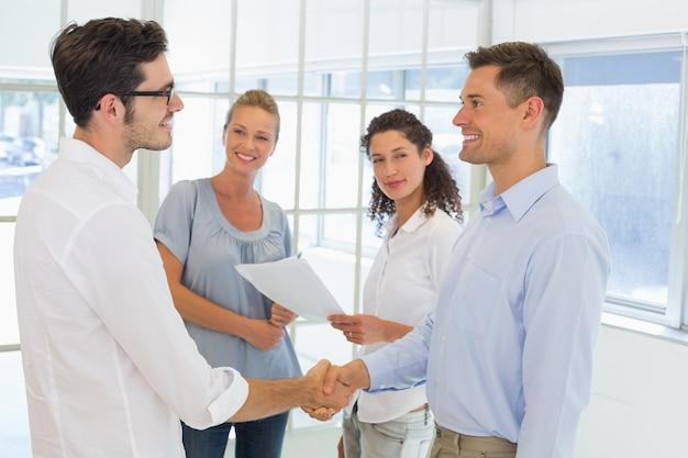 Przypadkowi biznesmeni trząść ręki i ono uśmiecha się