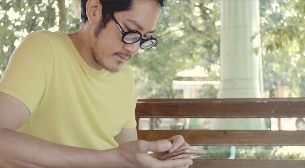 Przypadkowy azjatykci mężczyzna używa smartphone .checking poczta, rozmowa