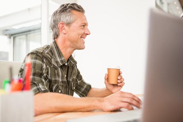 Przypadkowy biznesmen pracuje kawę i ma