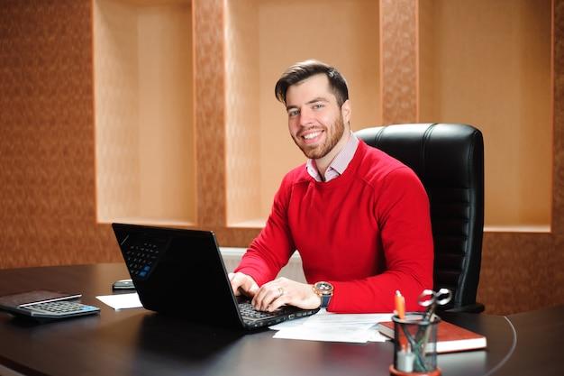 Przypadkowy biznesmen pracuje z komputerem w biurze
