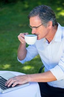 Przypadkowy biznesmen używa laptop i mieć kawę