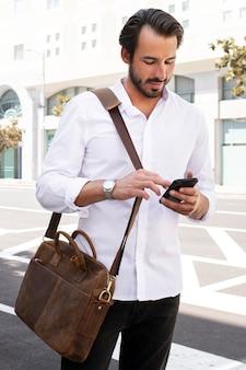 Przypadkowy biznesmen w białej koszuli w drodze do sesji zdjęciowej na świeżym powietrzu